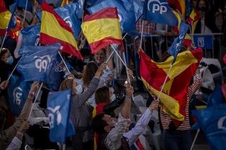 Priaznivci madridskej konzervatívnej prezidentky Isabel Diazovej Ayusovej mávajú vlajkami pred sídlom jej populárnej strany.