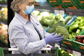 Senior woman wearing face mask and rubber gloves selects broccoli and other vegetables  in a supermarket -active elderly pensioners with trolley