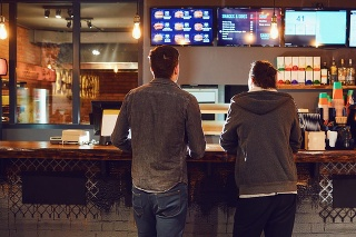 Rear view. Two men choose food in a fast food restaurant. Bar snack concept .