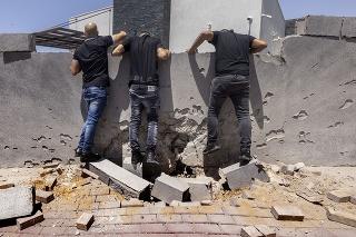 Ľudia sa pozerajú na zničený plot okolo domu po zásahu raketou vystrelenej z pásma Gazy, v meste Aškelon na juhu Izraela 11. mája 2021.