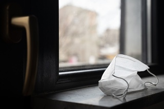 perspective view closeup of medical protection face mask left by the closed window near door handle quarantine concept