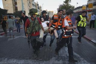 Armáda a zdravotníci odnášajú muža, ktorého postrelili v meste Lod.