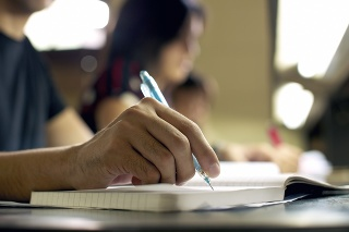 'Students doing homework and preparing exam at university, closeup of young man writing in college library'