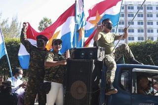 Stúpenci mjanmarskej armády  mávajú z auta vojenskými a národnými zástavami počas okružnej jazdy v Rangúne 2. februára 2021.