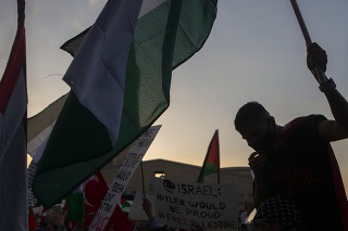 Palestínski stúpenci na proteste držia transparenty a palestínske zástavy.