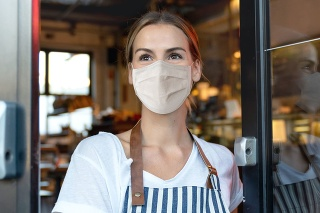 Happy business owner opening the door at a cafe wearing a facemask to avoid the spread of coronavirus – reopening after COVID-19 concepts