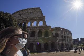 Turisti s ochrannými rúškami kráčajú popri antickom Koloseu v Ríme.