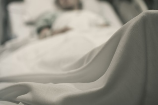 Sick woman lying in the hospital bed.