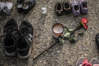 Detské topánky, tenistky a červená ruža sú na chodníku na pamiatku viac než 200 detí, ktorých pozostatky objavili v masovom hrobe.