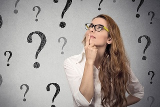 Thinking business woman with glasses looking up at many question marks isolated on gray wall background