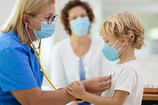 Pediatrician doctor examining sick child in face mask. Ill boy in health clinic for test and screening. Kids home treatment of virus. Coronavirus pandemic. Covid-19 outbreak. Patient coughing.