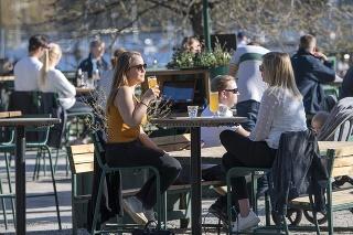 Apríl 2020:  Ľudia počas epidémie koronavírusu na terase baru v Štokholme.