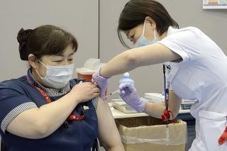 Zdravotná sestra dostáva prvú dávku vakcíny proti ochoreniu COVID-19