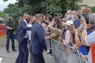 Na videosnímke francúzsky prezident Emmanuel Macron (uprostred) dostáva facku od muža (v zelenom tričku) počas Macronovej návštevy  v obci Tain-l'Hermitage.