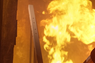 Building is On Fire. Fireman is Going Upstairs. Open Flames are Seen on Stairs.