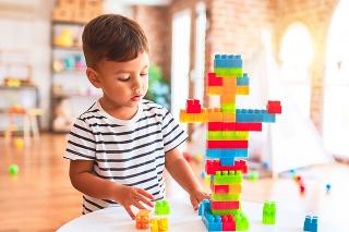 Beautiful toddler boy playing with construction blocks at kindergarten