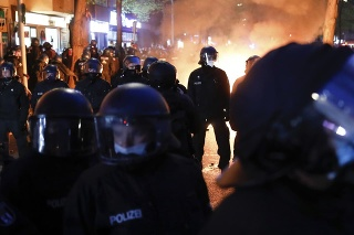 Policajti stoja pred ohňom, ktorý založili demonštranti počas zhromaždenia.