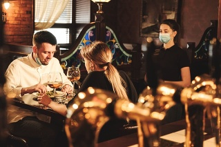 Waitress with protective mask service clients at bar, pub, café or restaurant. Reopen after quarantine restrictions. COVID - 19 Concept