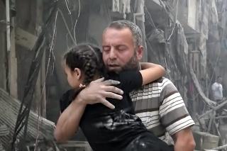 Muž nesie na rukách dieťa po náletoch v povstalcami ovládanej časti mesta Aleppo.