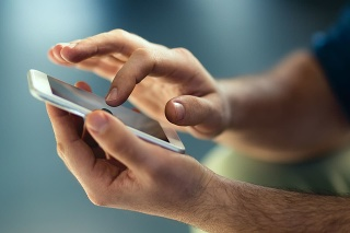 Male hands typing on smartphone.