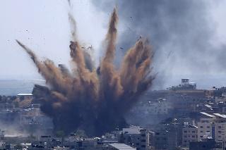 Po izraelských náletoch na budovu v Gaze vo štvrtok 13. mája 2021 stúpa dym.