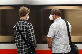 Muži s ochrannými rúškami na zastávke metra v Prahe.