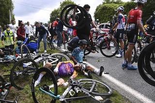 Na snímke taliansky cyklista Kristian Sbaragli (vľavo) a francúzsky cyklista Bryan Coquard (vpravo) ležia na zemi po páde v prvej etape cyklistických pretekov Tour de France z Brestu do Landerneau (197,8 kilometrov) 26. júna 2021.