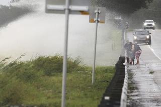 Vlny sa valia cez hrádzu na štátnu diaľnicu 20 neďaleko pláže Choctaw Beach na Floride počas vyčíňania hurikánu