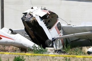 A small airplane crashed in a field near a big warehouse building.