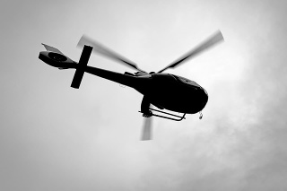 Black and white silhouette of helicopter from low angle view
