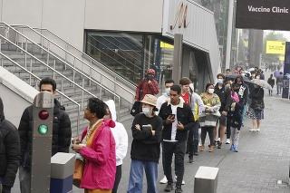 Ľudia v Londýne čakajú v rade na očkovanie proti COVID-19.