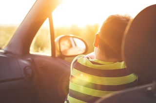 Boy on front seat of a car looking at camera in sunset