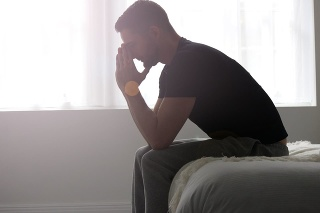 A man sitting at the end of a bed, deep in solemn thought.