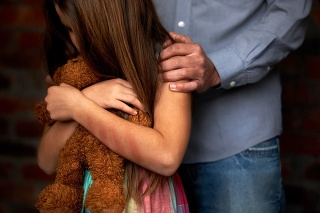 Abused little girl with her abuser gripping her shoulder