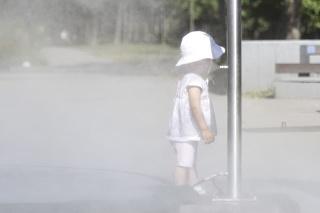 Dieťa prechádza hmlovou bránou počas horúceho letného dňa.
