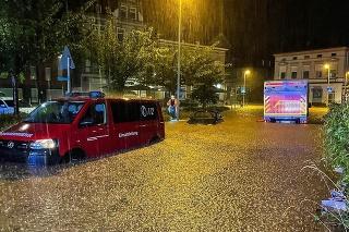 Hasičské auto a dodávka sú odparkované na zaplavenej ceste v meste Hagen.
