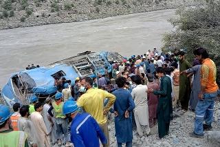 Miestni obyvatelia a záchranári stoja neďaleko autobusu, ktorý sa zrútil po výbuchu do rokliny