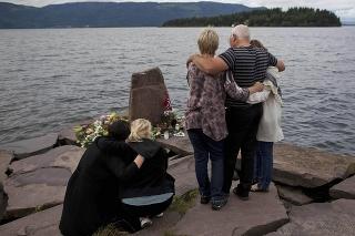 Príbuzní obetí počas minúty ticha, v pozadí nórsky ostrov Utöya.