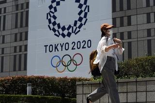 Žena kráča okolo bannera pre letné olympijské hry.