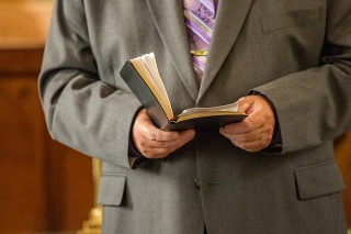 Wedding Pastor Reading from Bible in Church
