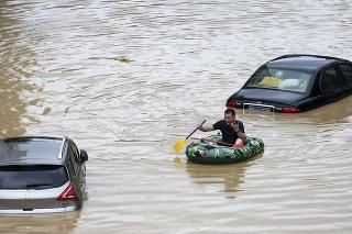 Muž sa brodí na člne po zaplavenej ceste v provincii Kuang-si Čuang na juhu Číny.