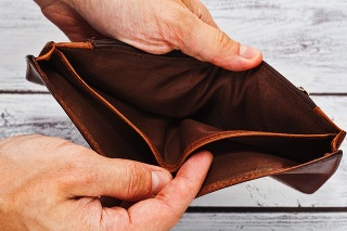 Person holding in hands totally empty leather wallet - crisis and poverty symbol