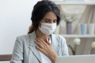 Business woman in mask sitting at desk feels unhealthy put hand where is lungs, suffering from repeated coughing and breath difficulties. Risk coronavirus 2019-ncov contamination at workplace concept