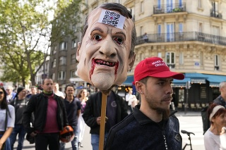 Demonštrant drží masku s podobizňou francúzskeho prezidenta Emmanuela Macrona počas demonštrácie v Paríži.