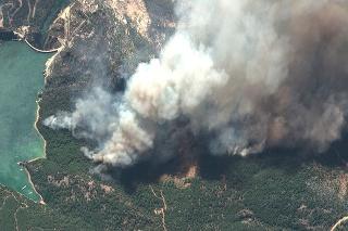Na satelitnej snímke hustý dym stúpa počas lesného požiaru neďaleko priehrady Oymapinar na juhu Turecka.
