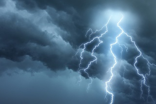 Bright lightning illuminates dark cloudy sky during a thunderstorm. Natural dangers and majestic beauty. Real cloudscape with computer generated lightning. Copy space on image side.