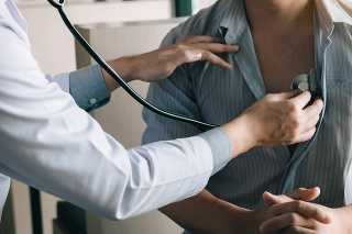 Asian doctor is using a stethoscope listen to the heartbeat of the elderly patient.