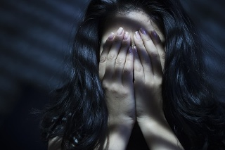Indoor image of a young woman covering her face with her both hands out of embracement and sadness. Striped Light and shadows are falling on her through blinds. One person, low key, horizontal composition with selective focus and copy space.