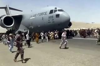 Ľudia bežia okolo amerického transportného lietadla C-17 na medzinárodnom letisku Hámida Karzaja.