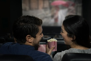 Happy Latin American couple lauging at the movies eating popcorn and having fun